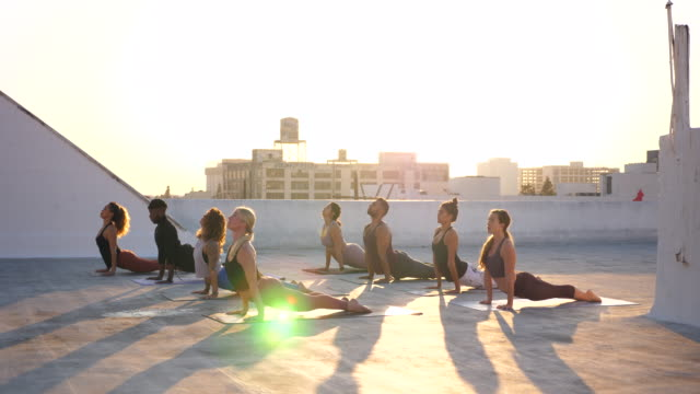 stockvideo's en b-roll-footage met ms yoga class practicing on rooftop at sunset - ondergoed