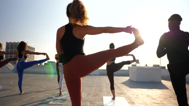 ms yoga class practicing on rooftop at sunset - balance stock videos & royalty-free footage