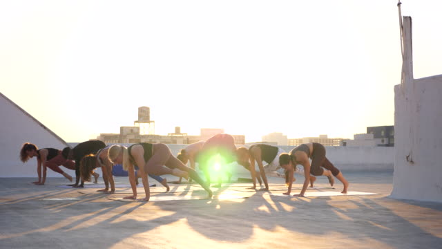 ms yoga class practicing on rooftop at sunset - tights stock videos & royalty-free footage