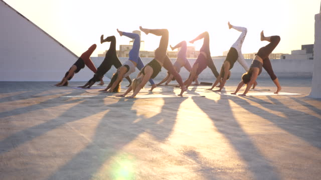 ms yoga class practicing on rooftop at sunset - leggings stock videos & royalty-free footage