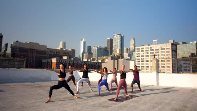 ws yoga class practicing on rooftop overlooking city - tights stock videos & royalty-free footage