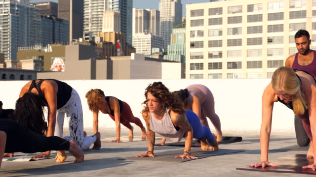 ms yoga class practicing on rooftop overlooking city - vest stock videos & royalty-free footage