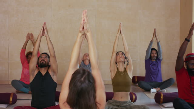 yoga class raising arms and relaxing in yoga studio - cross legged stock videos & royalty-free footage