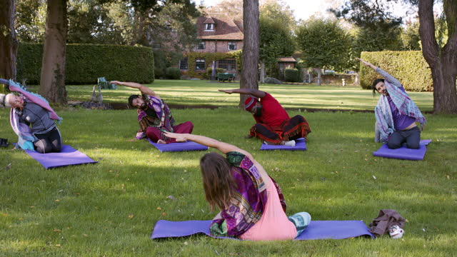 yoga class stretching on mats in park - kent england stock videos & royalty-free footage