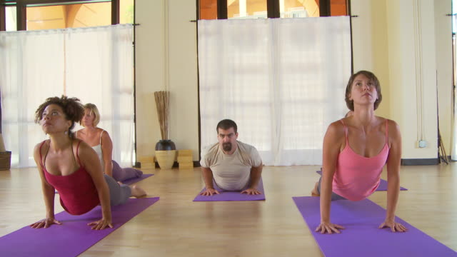 yoga class - sun salutation stock videos and b-roll footage