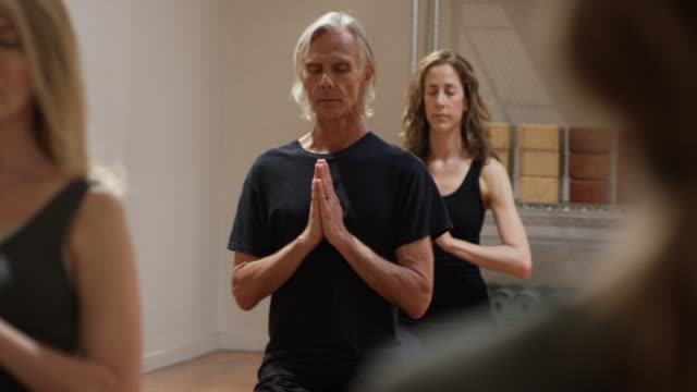 Yoga class with healthy retired seniors and older adults in a studio.
