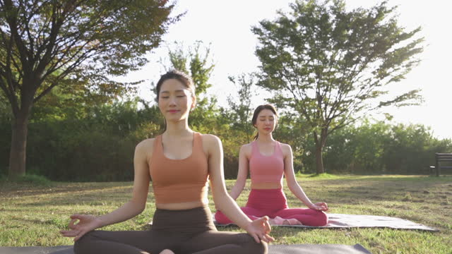 vídeos y material grabado en eventos de stock de yoga in city - yoga instructor and young woman meditating while sitting on yoga mat - sin mangas