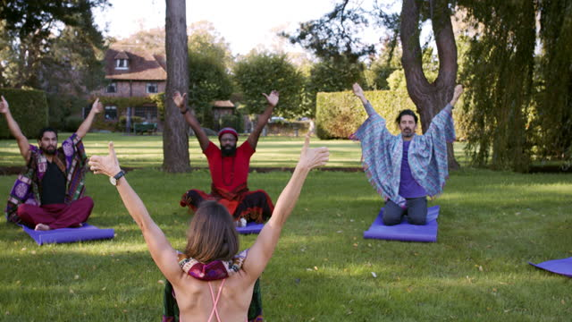 yoga instructor and students practising outdoors with arms raised - grass family stock videos & royalty-free footage