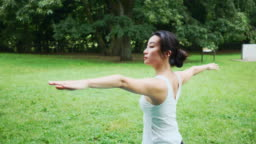 Yoga instructor doing warrior pose in public park