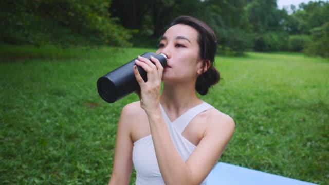 公共の公園でステンレスボトルから水を飲むヨガインストラクター - ウォーターボトル点の映像素材/bロール