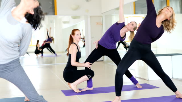 Yoga instructor guiding women at health club