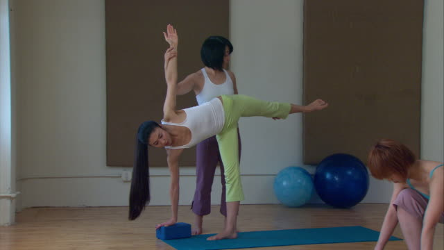 MS Yoga instructor helping student assume the Half-Moon Position/ New York, NY