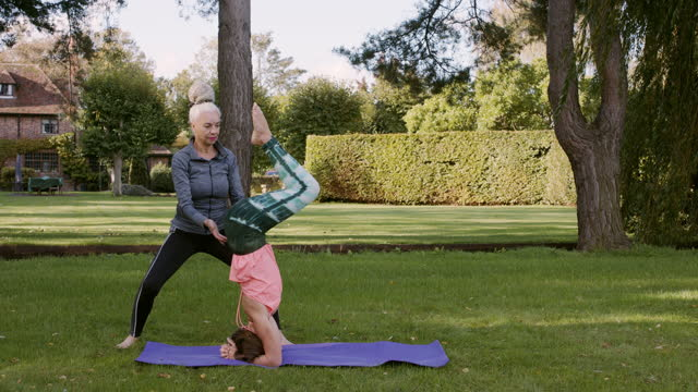 yoga instructor helping student to complete yoga headstand - adjusting stock videos & royalty-free footage