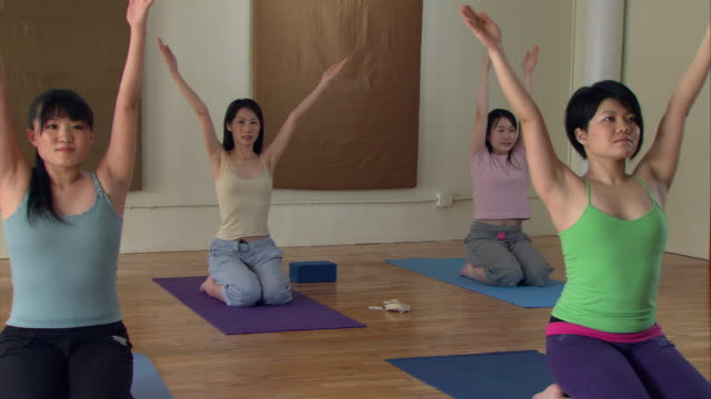 ms pan yoga instructor leading class in exercises/ new york,  ny - 35 39 jahre stock-videos und b-roll-filmmaterial