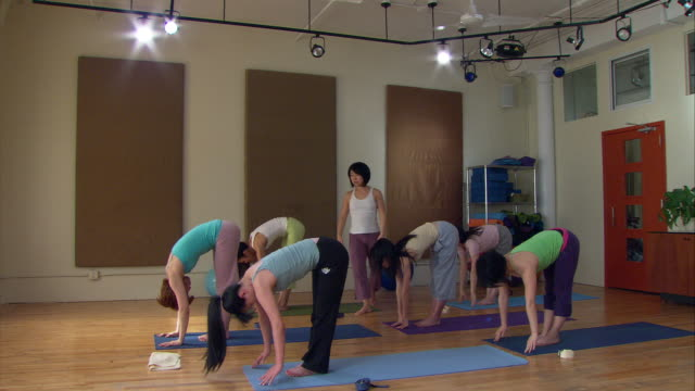 WS ZI Yoga instructor leading class in series of exercises/ New York,  NY