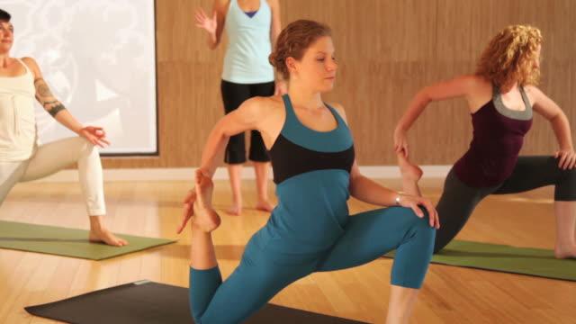 stockvideo's en b-roll-footage met ws yoga instructor leading class through various yoga poses / austin, texas, usa - benen gespreid