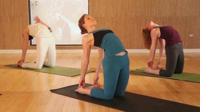 WS TU Yoga Instructor Leading Class Through Various Poses Austin Texas USA