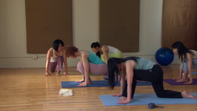 vídeos y material grabado en eventos de stock de ms td pan yoga instructor leading three women through poses/ new york, ny - centro de yoga