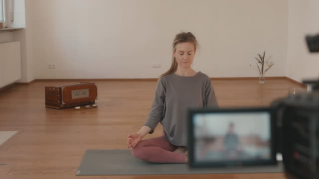 yoga instructor recording lesson alone in studio - mindfulness stock videos & royalty-free footage
