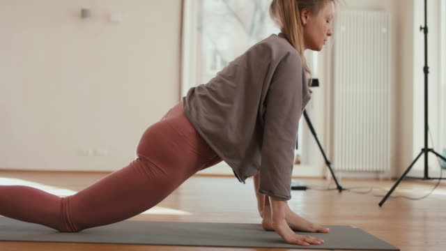 vídeos de stock, filmes e b-roll de yoga instructor recording lesson alone in studio - tutorial