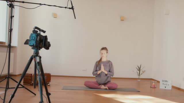 vidéos et rushes de yoga instructor recording lesson alone in studio - blog