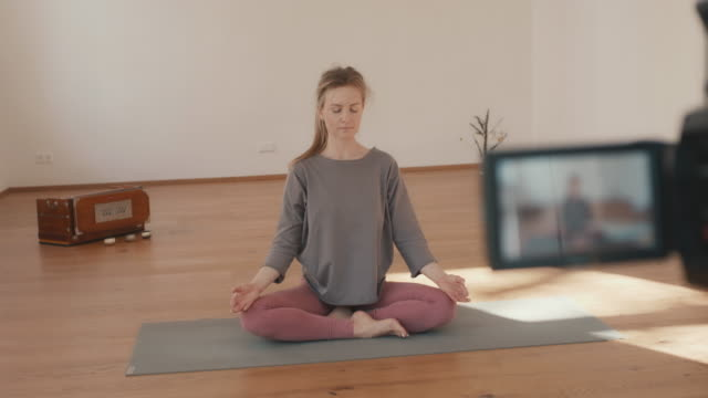 yoga instructor recording lesson alone in studio - meditating stock videos & royalty-free footage