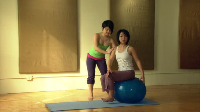 WS Yoga instructor showing position to woman sitting on exercise ball/ New York, NY