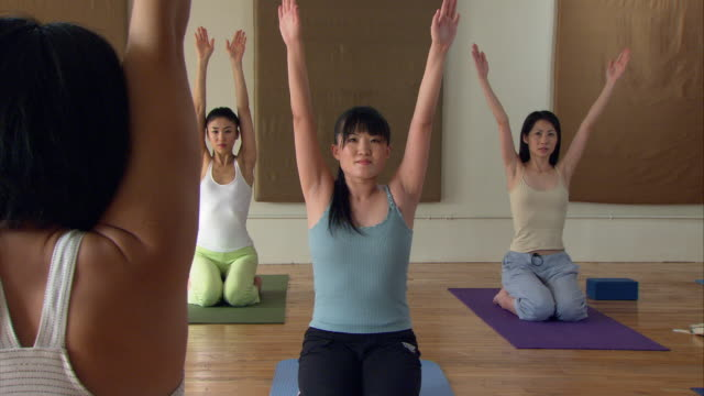 WS ZI Yoga instructor showing woman how to lie on yoga blocks during a class/ New York,  NY