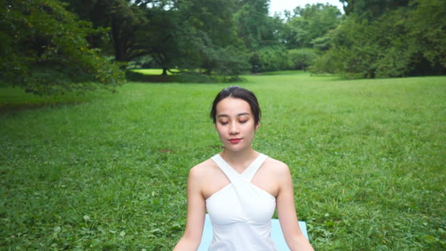 yoga instructor sitting in lotus position in nature - tilt up - lotus position stock videos & royalty-free footage