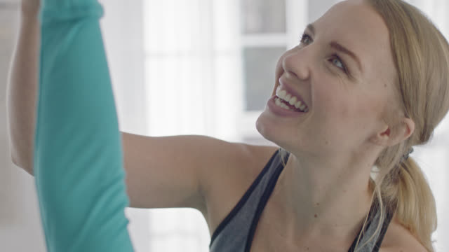 SLO MO. Yoga instructor smiles as she helps client with Triangle pose.