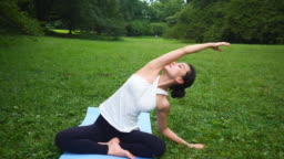 Yoga instructor stretching hand in lotus position in nature
