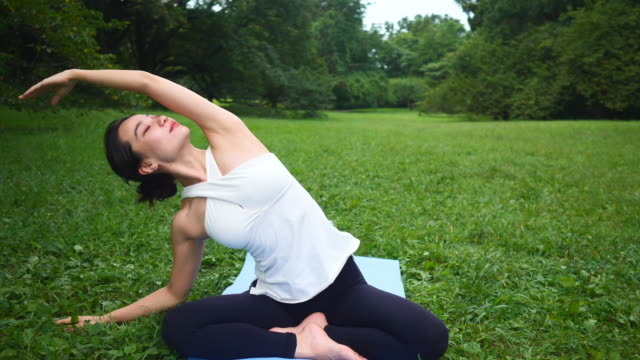 yoga instructor stretching hand in lotus position in nature - lotus position stock videos & royalty-free footage