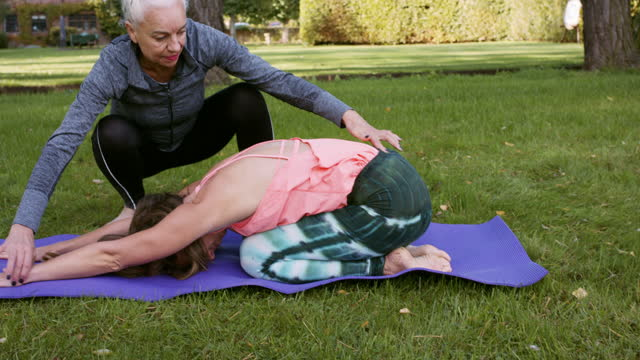 yoga instructor teaching student to complete advanced yoga position - adjusting stock videos & royalty-free footage