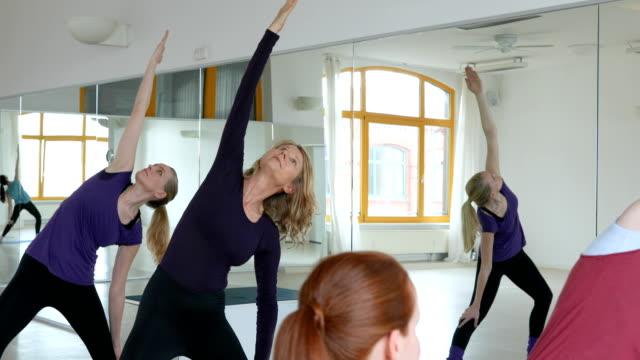 Yoga instructor teaching women at health club