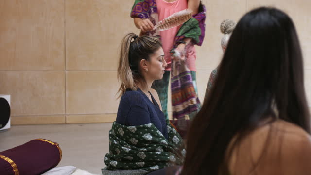 Yoga instructor using smudge stick in class of students
