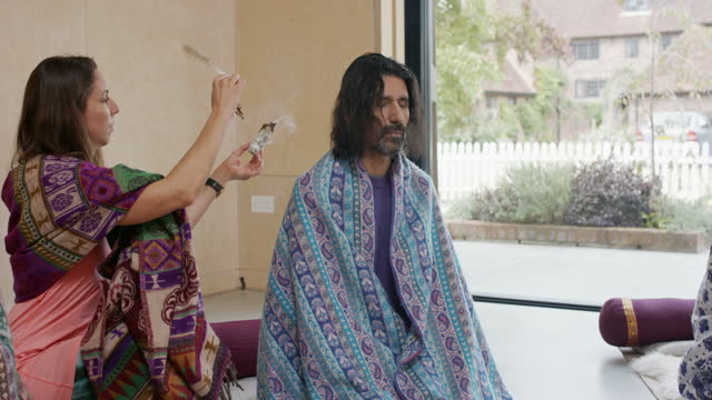 Yoga instructor using smudge stick therapy on mature man in yoga studio