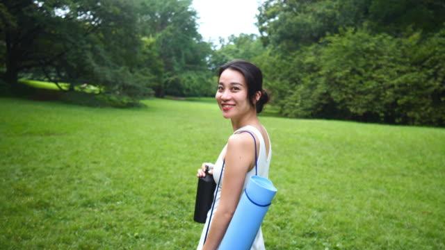 公共公園でレッスンのために歩くヨガインストラクター - ウォーターボトル点の映像素材/bロール