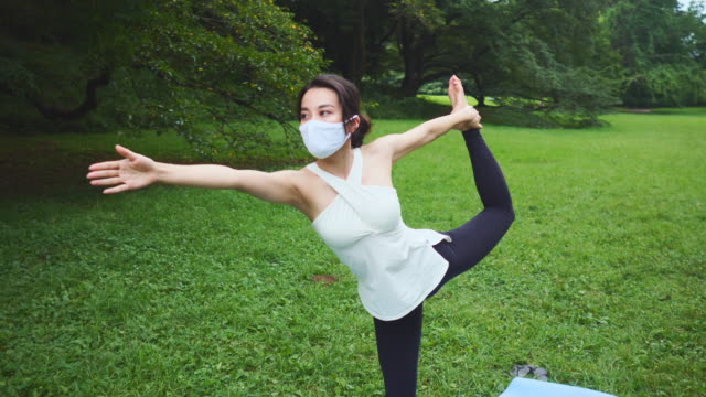 vídeos de stock, filmes e b-roll de instrutor de yoga com máscara facial protetora em pé em uma perna e mão esticando em parque público - yoga