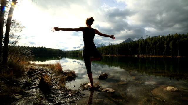 vídeos de stock, filmes e b-roll de ioga movimentos by the lake, jovem mulher - pose de arvore