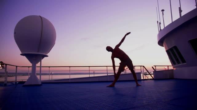 vídeos de stock e filmes b-roll de ioga no barco de manhã cedo-utthita trikonasana - navio de passageiros