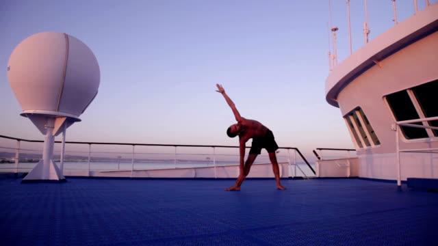 Yoga on ship in the evening - parsvakonasana and trikonasana
