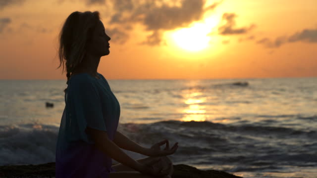 ビーチでヨガ。蓮のポーズで瞑想の女性。サンセット