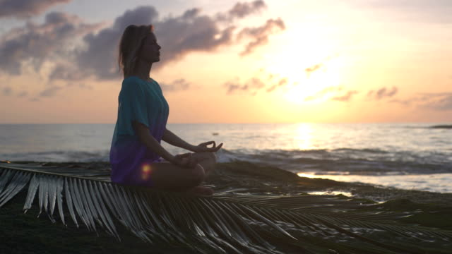 Yoga on the beach. Woman meditating in lotus pose. Sunset