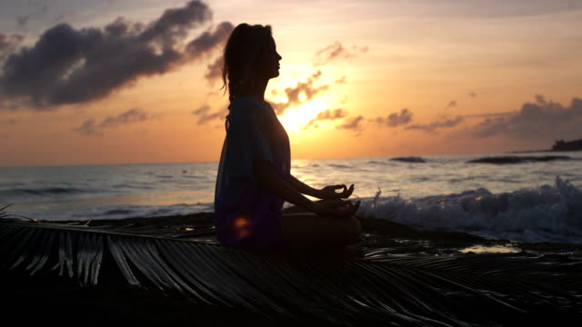 Yoga am Strand. Frau in Lotus-Pose zu meditieren. Sonnenuntergang