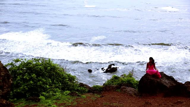 vídeos y material grabado en eventos de stock de yoga en la costa, goa - con las piernas cruzadas
