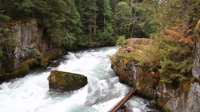 yoga on the rocks above the river - lotus position stock videos & royalty-free footage