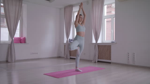 yoga practiced by woman stretching seated lotus poses prayer position in a dance studio. - slow motion - lotus position stock videos & royalty-free footage