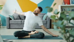 Yoga student learning asanas online using laptop at home exercising on mat