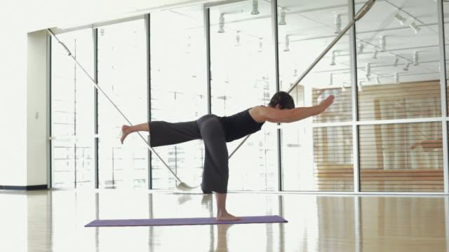 ws yoga student practicing yoga in yoga studio / vancouver, british columbia, canada - auf einem bein stock-videos und b-roll-filmmaterial