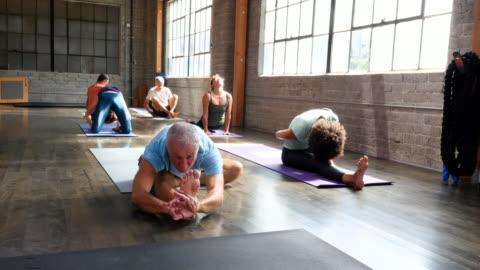 ms pan yoga students in various poses during class in studio - 50 54 år bildbanksvideor och videomaterial från bakom kulisserna